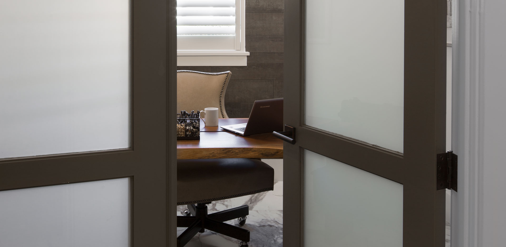 Looking into an office through a pair of TS3000 doors in MDF with white lami glass