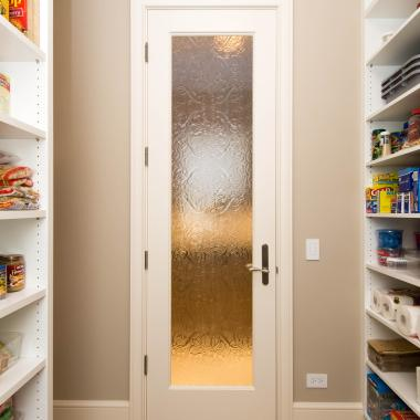 Glass was used in this FL100 pantry door brings light into the adjoining butler's pantry. MDF with quarter round (QR) sash and custom glass