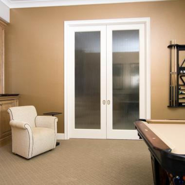Game room featuring a pair of FL100 pocket doors in MDF with quarter round (QR) sticking and custom glass.