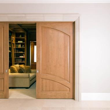 A common arch pair of cherry pocket doors open to a study. TS2050 in cherry with quarter round (QR) sticking and raised (A) panel.