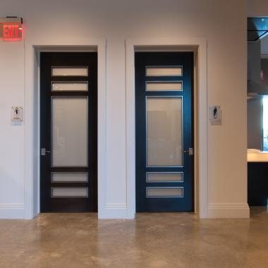 This dealer showroom features stunning TS5080 doors in white oak and white lami glass with quirk (QM) moulding and metal inlay.