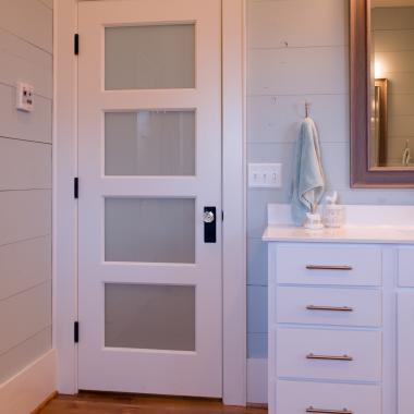 Farmhouse bathroom with TS4100 doors in MDF with quarter bead (QB) sticking and White Lami glass.