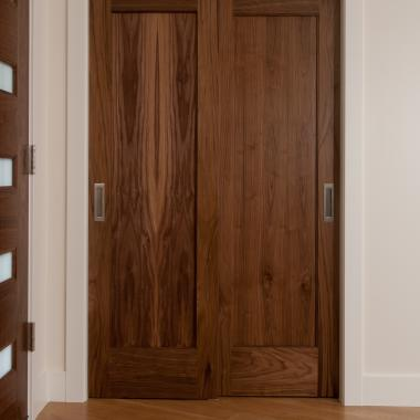 Pair of TM1000 bypass closet doors in walnut with one step (OS) sticking and flat (C) panel
