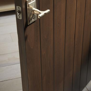 Detail of plank door (VG1000) in select alder with standard V-groove profile with Cinnamon stain with Rustic Antiquing package
