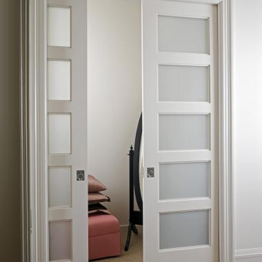 Substituting panels with White Lami glass on these TS500 pocket doors allows light into a walk-in closet.
