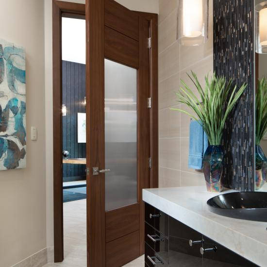 A TM9250 door, in walnut with Nutmeg stain and Groove glass, divides a bathroom from this contemporary study.