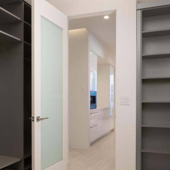 White Lami glass creates total privacy while adding a modern aesthetic. This closet door features a mirror on the back side for functionality and style.