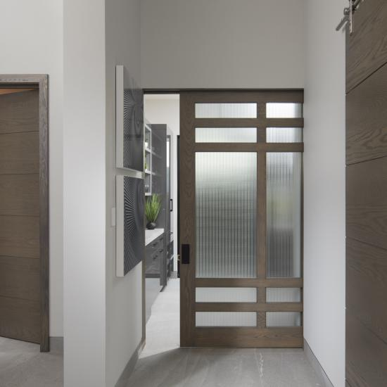 A TS5080 barn door, in plain sawn white oak with Grey Mist handwiped stain, square stick sticking and Dash glass, is flanked by TMIR6000 doors