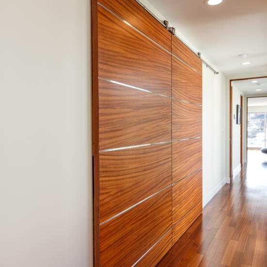 "Pair of TMIR6080 barn doors in mahogany with ½"" brushed stainless steel inlay."