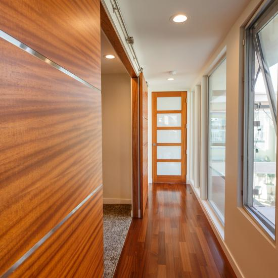 "Hallway with pair of TMIR6080 barn doors in mahogany with ½"" brushed stainless steel inlay. On Right, TS5000."