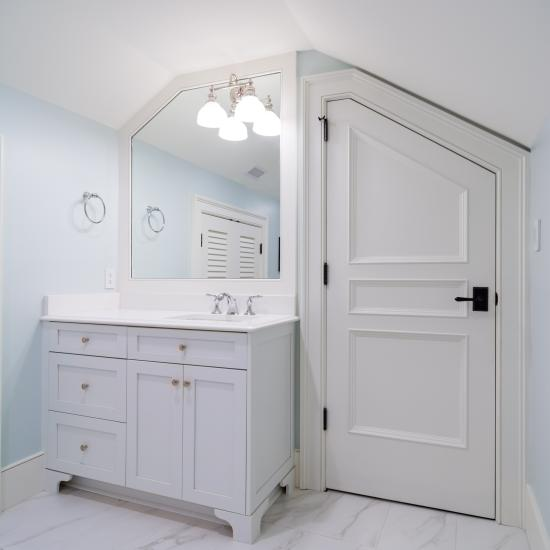 A clipped-corner TS3070 door fits the unique ceiling of this attic powder room.