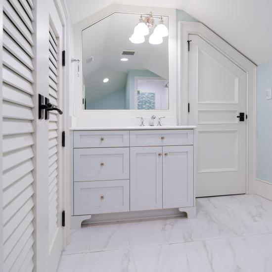 A clipped-corner TS3070 door fits the unique ceiling of this attic powder room. Pair of LVR1000 doors to the left.