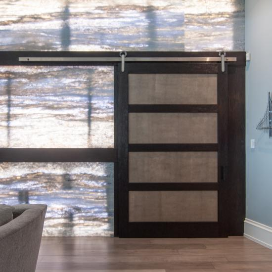 This massive barn door with wire-brushed white oak and Edelman shagreen leather makes a statement against a wall of backlit calcite.