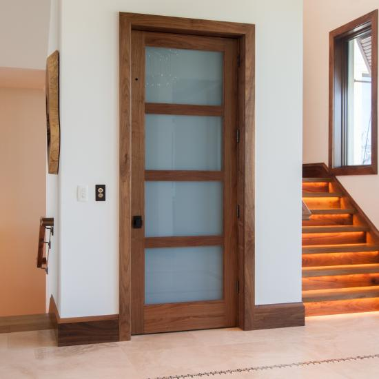 Elevator door in walnut with white lami glass