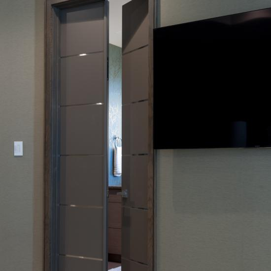 Entry to bathroom feature TMIR6000 doors in MDF with bright stainless inlay.