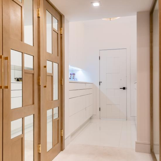 The designer added glamour to this walk-in closet by custom applying plant-ons and mirrors to TS3000 doors in MDF.