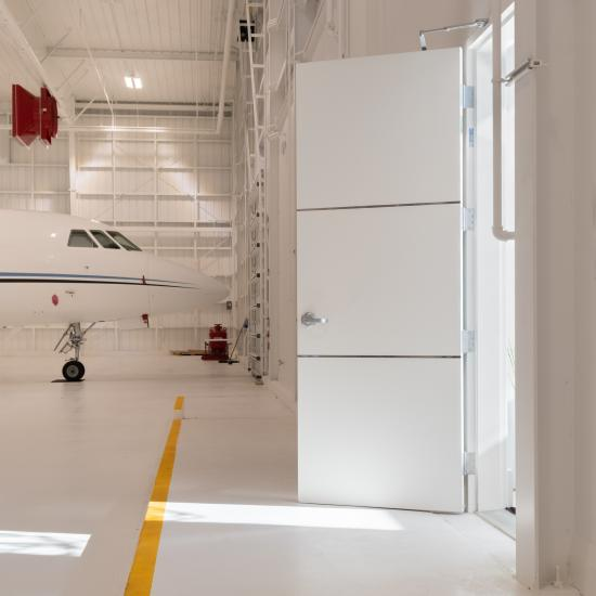 "The lounge of this this private jet hangar features TMIR3000 doors in MDF with ½"" bright stainless steel inlays."