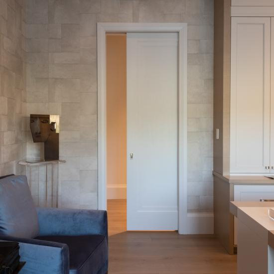 A TS1000 pocket door, in MDF with Miracle (MR) moulding and Flat (C) panel separate a private office from the hallway.