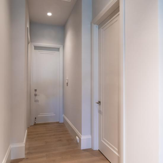 A hallway with TS1000 doors, in MDF with Miracle (MR) moulding and Flat (C) panel lead downs to the garage.