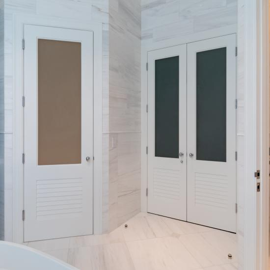 A master bath features TS2060 doors in MDF with Roman Ogee (OG) sticking, Raised (A) panel and Frosted Glass. The bottom panels have been replaced with false louver panels.