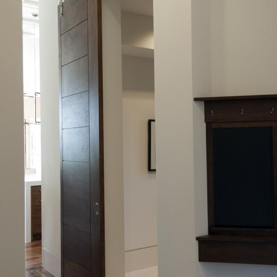 TM9000 sliding barn door in walnut with asymmetric stiles and kerf cut reveal.
