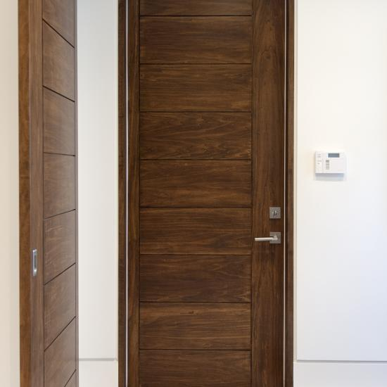 TM9000 house-to-garage fire door in walnut with asymmetric stiles and kerf cut reveal