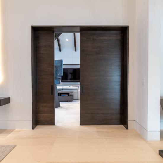 "A pair of TMIR3080 pocket doors, in quarter sawn white oak with ¼"" kerf cut reveals, open to a family room. Builder provided stain finish.int"