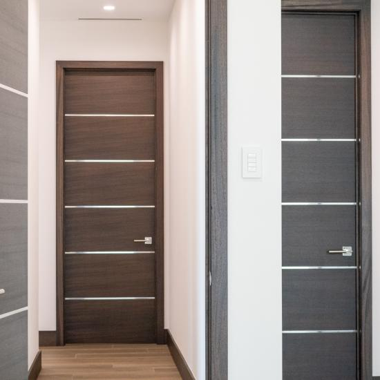 "This bedroom features TMIR6000 doors in mahogany with ½"" bright stainless steel inlay. Builder provided stain finish."