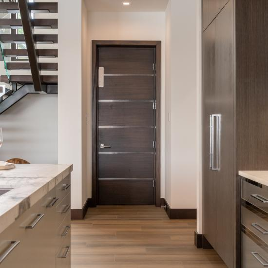 "An elevator features a TMIR6000 door in mahogany with ½"" bright stainless steel inlay. Builder provided stain finish."