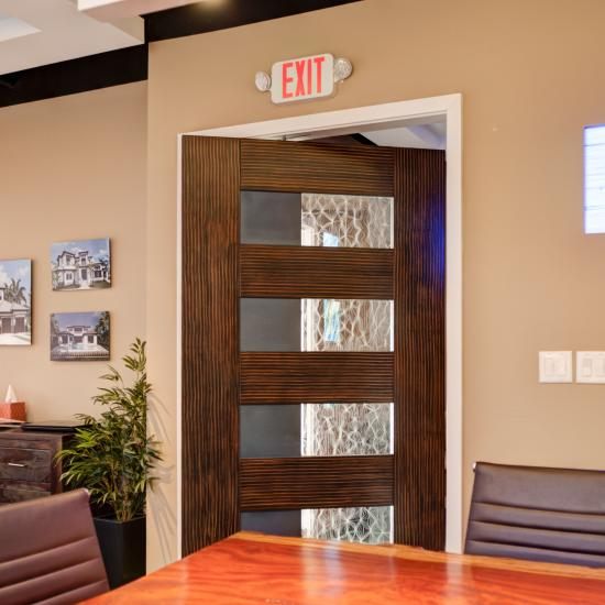 The conference room of this design studio features a TM9160 pivot door in MDF with Merletto glass. The door is painted faux wood on one side, faux alligator on the reverse.