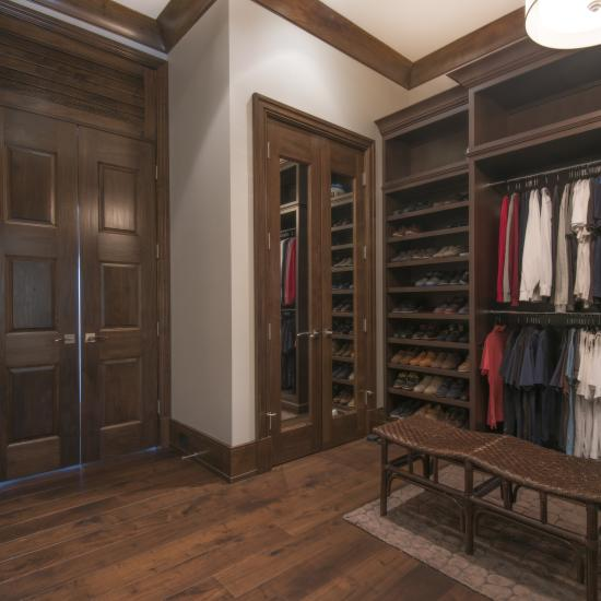 Luxury walk-in closet features a pair of TS1000 doors in walnut with Roman Ogee (OG) sticking and built-in mirrors. To the left, a pair of TS3000 doors.