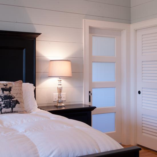 Farmhouse bedroom with TS4100 doors in MDF with quarter bead (QB) sticking and White Lami glass.