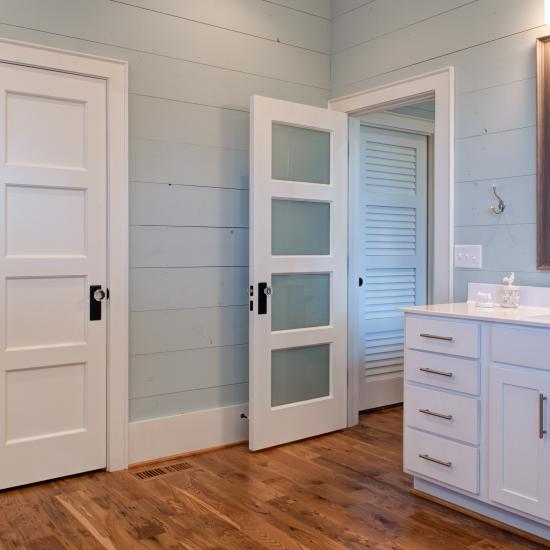 Farmhouse bathroom with TS4100 doors in MDF with quarter bead (QB) sticking and White Lami glass or flat (C) panel. TS4100 louver door in background.