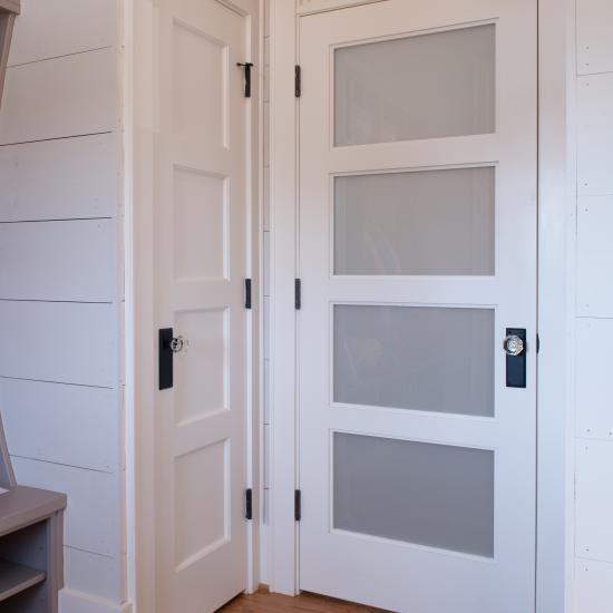 Farmhouse mudroom with TS4100 doors in MDF with quarter bead (QB) sticking and White Lami glass.