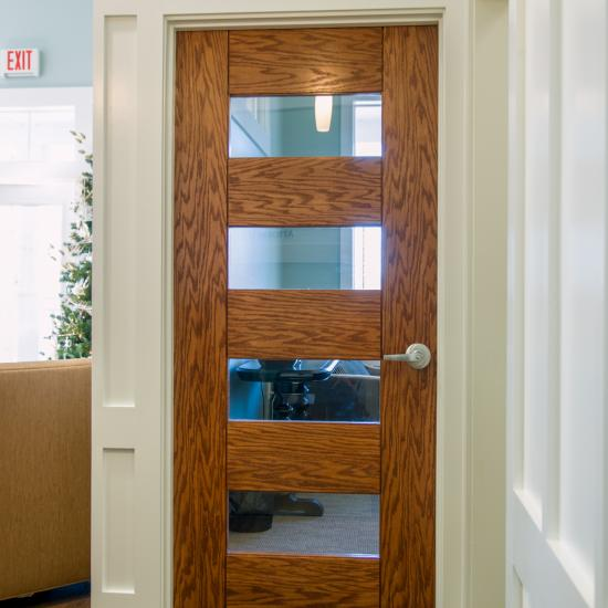 "Office featuring TM9160 in Red Oak with clear glass and 1/4"" kerf cut reveal."
