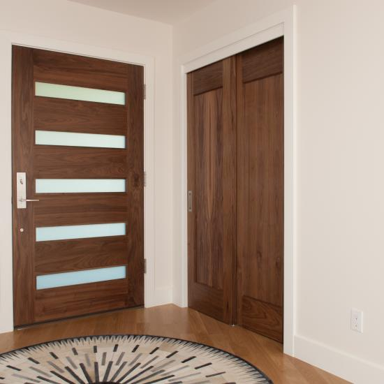 Interior view of TM5100 exterior door in walnut with white lami glass and pair of TM1000 bypass closet doors in walnut with one step (OS) sticking and flat (C) panel