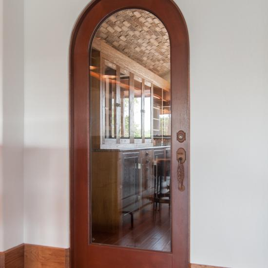 Wine cellar featuring a radius-top TS1050 in white oak with clear glass.