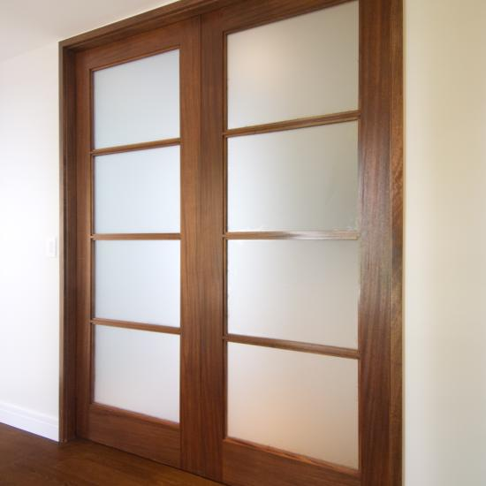Pair of FL400 pocket doors in walnut with square stick (SS) sash and frosted glass