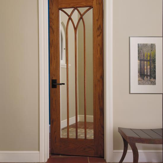 Gothic-inspired door in wire-brushed white oak with cove & bead (CB) sash and double-sided mirror panels.