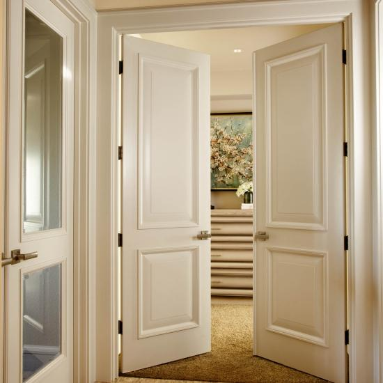 Pair of TS2020 doors in MDF with senior raised (E) panel and custom sticking that matches moulding used throughout the home.
