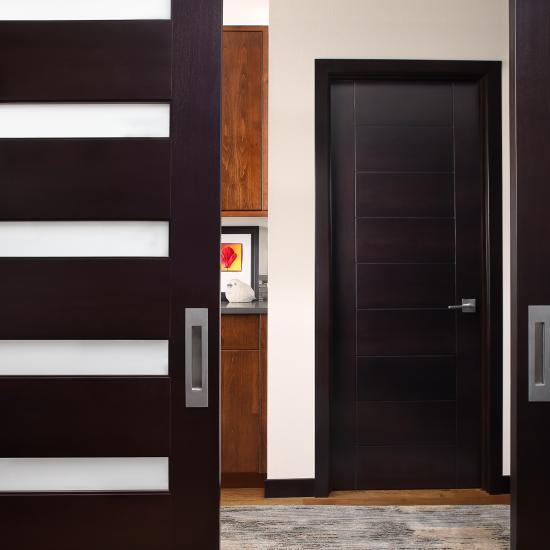 A pair of TM6100 barn doors in select alder with Espresso hand-wiped stain and White Lami glass. TM9000 powder room door in back.