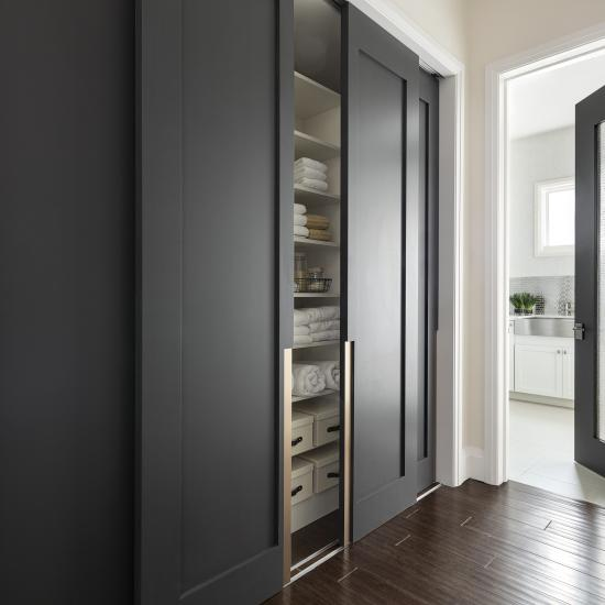 TM1000 double bypass doors in MDF with Chemetal bronze insert flank the hallway leading to the laundry room which features 3Form resin insert; Home designed by Marc-Michaels