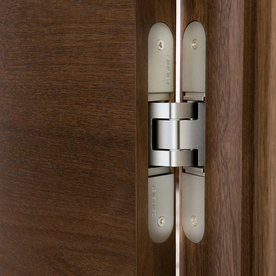 Detail of Simonswerk concealed hinge in TMF1000 flush door (walnut with Cappuccino stain).
