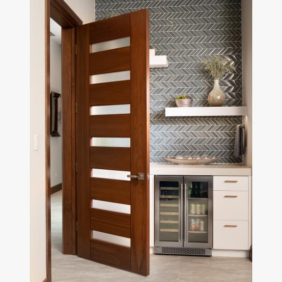 A TM9350 door in walnut with Nutmeg stain and Dash glass opens to a guest suite