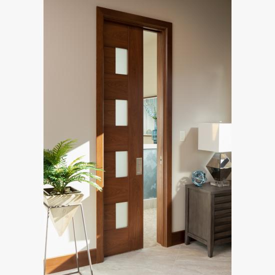 A TM9400 door, in walnut with Nutmeg stain and Frosted glass, divides the bathroom from the rest of this guest suite