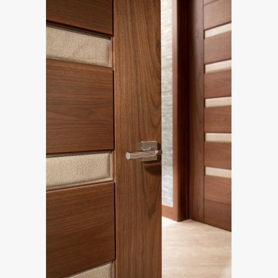 A TM9340 door, in walnut with Nutmeg stain and Shagreen Café Latte leather, opens to a large study which doubles as a guest room.