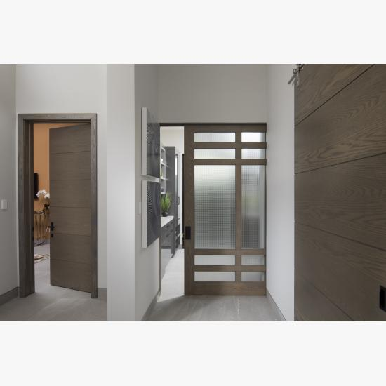 A TS5080 pocket door, in plain sawn white oak with Grey Mist handwiped stain, square stick sticking and Dash glass, is flanked by TMIR6000 doors