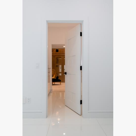 A TM9420 door in MDF open to a luxurious walk-in closet.