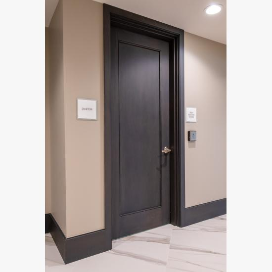 Condominium tower featuring TS1000 doors, in rift sawn white oak with Quirk (QM) moulding and Flat (C) panel in lobby.