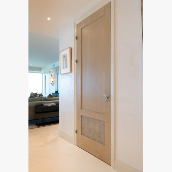 This modified TS2210 door, in wire-brushed plain sawn white oak with customer applied ceruse finish and Shagreen Grey Oyster leather, features olive knuckle hinges.